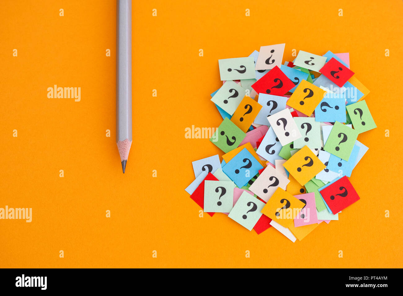 Pencil and question marks on yellow background. Concept image. Close up. Stock Photo