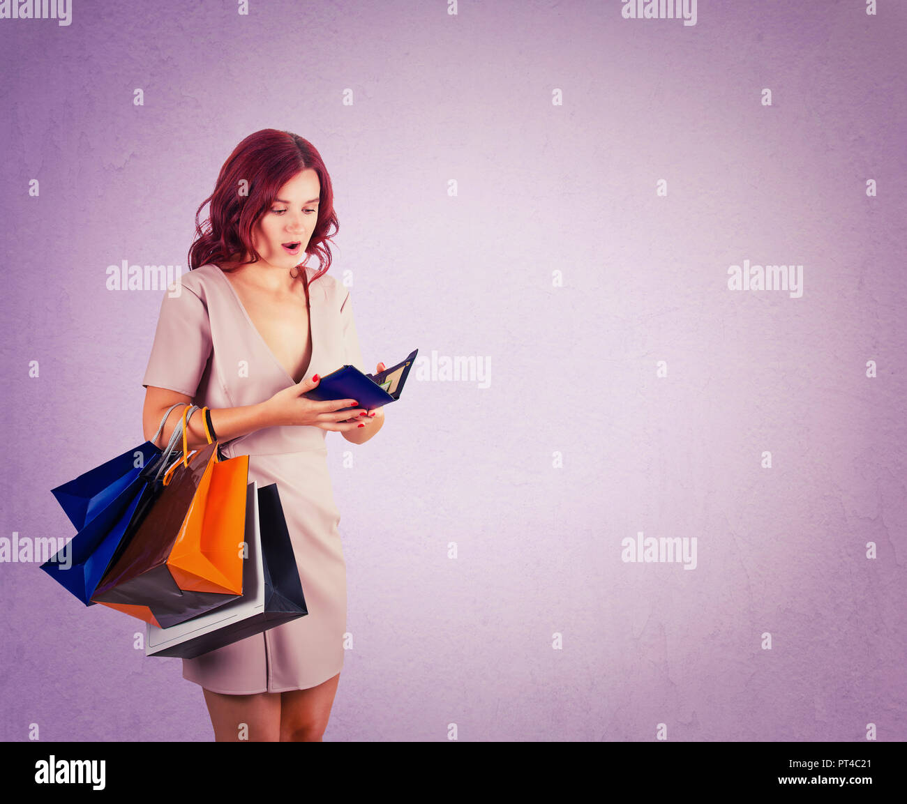 Shocked woman shopaholic carrying bags holding a empty wallet, has no money for shopping in her pouch isolated over purple background with copy space. - Stock Image