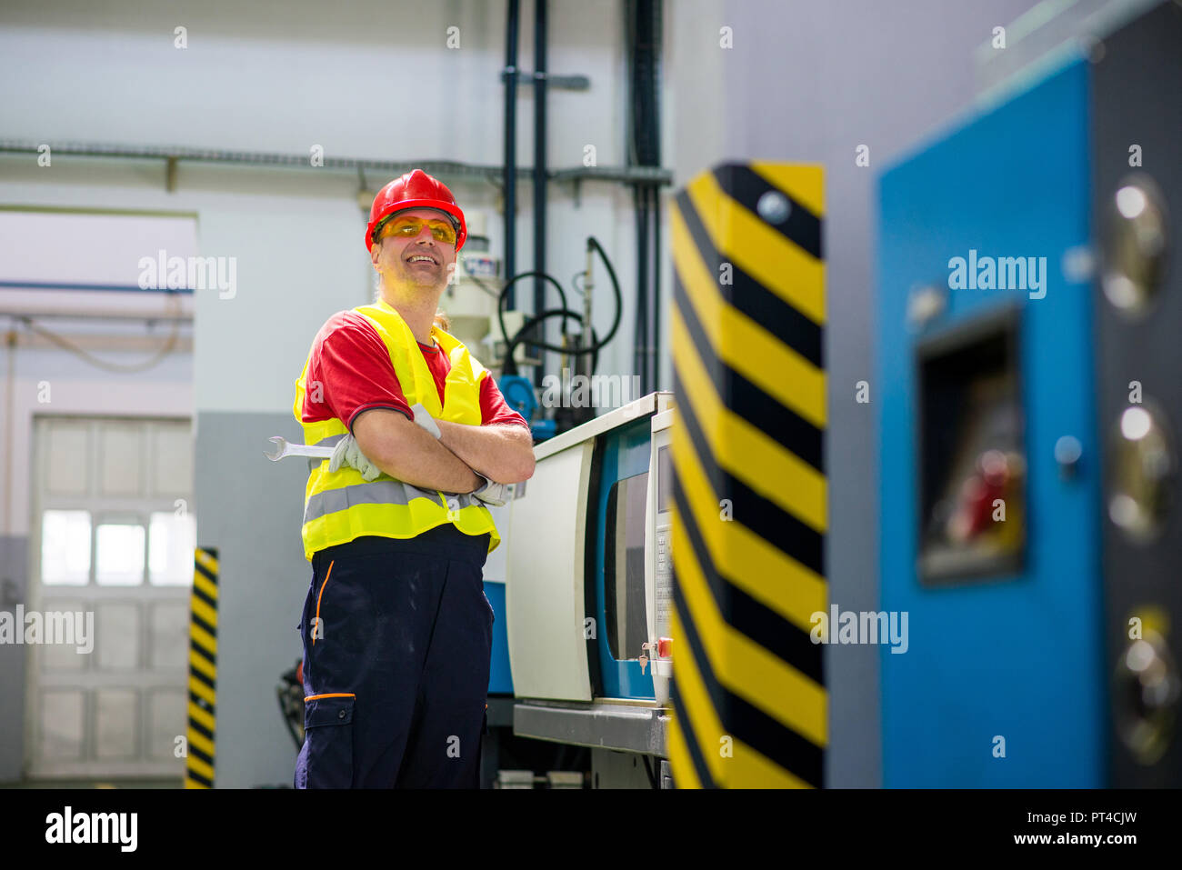 Smiling factory technician beside a machine - Stock Image