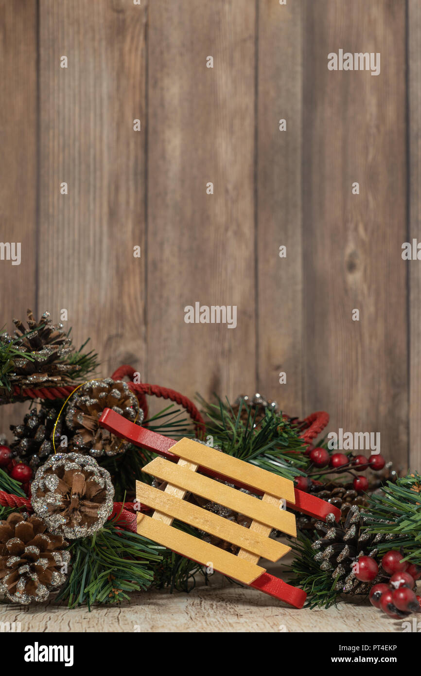 Christmas decor with pinecones and wooden sled on wood background ...