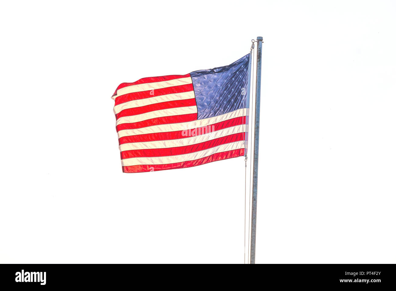 United States flag flying on a flag pole aganist a white background - Stock Image