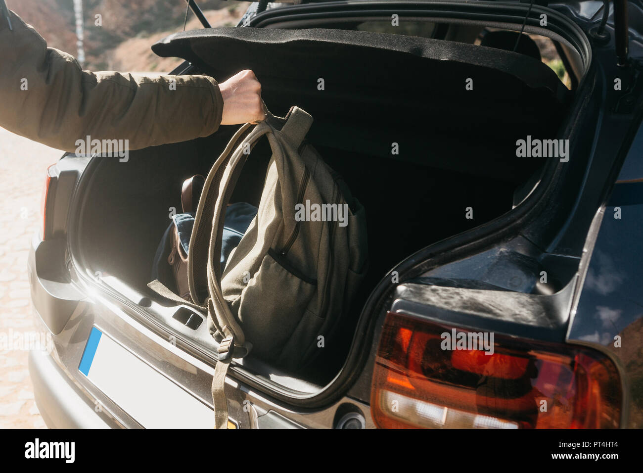 A man or a tourist puts a backpack in the trunk of a car. Preparation for the trip. The concept of tourism or travel by car. Stock Photo