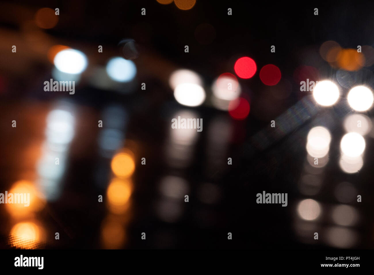 Blurred light from car headlights reflected from a wet road on a rainy night. - Stock Image