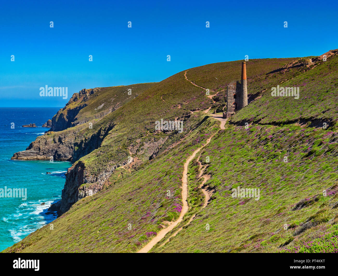The South West Coast Path, winding its way over the Cornish cliffs and passing by the Towenroath Engine House, part of the Wheal Coates Mine, Cornwall Stock Photo