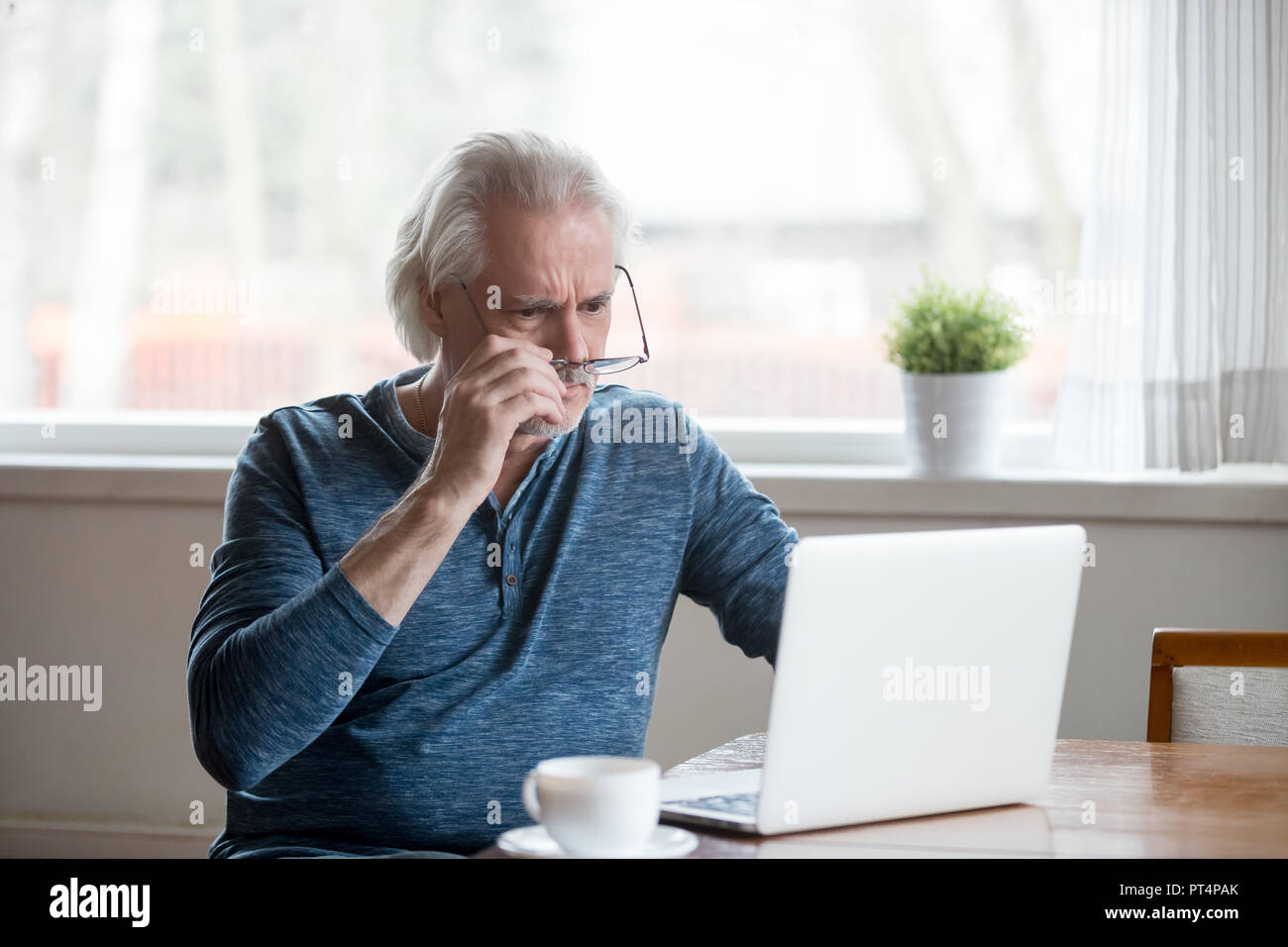 Shocked frustrated senior man taking off glasses looking at lapt - Stock Image