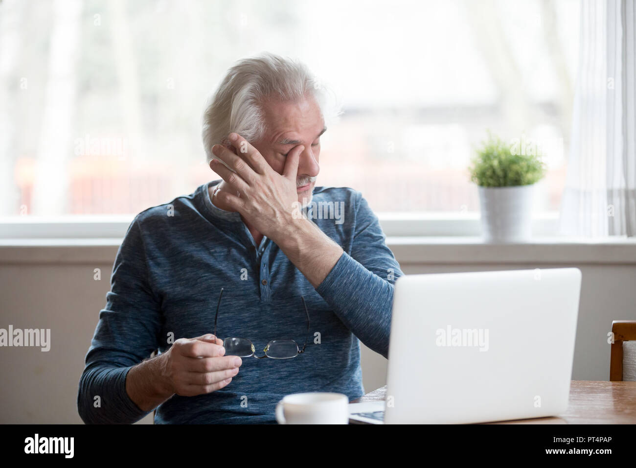 Fatigued mature man taking off glasses suffering from tired eyes - Stock Image