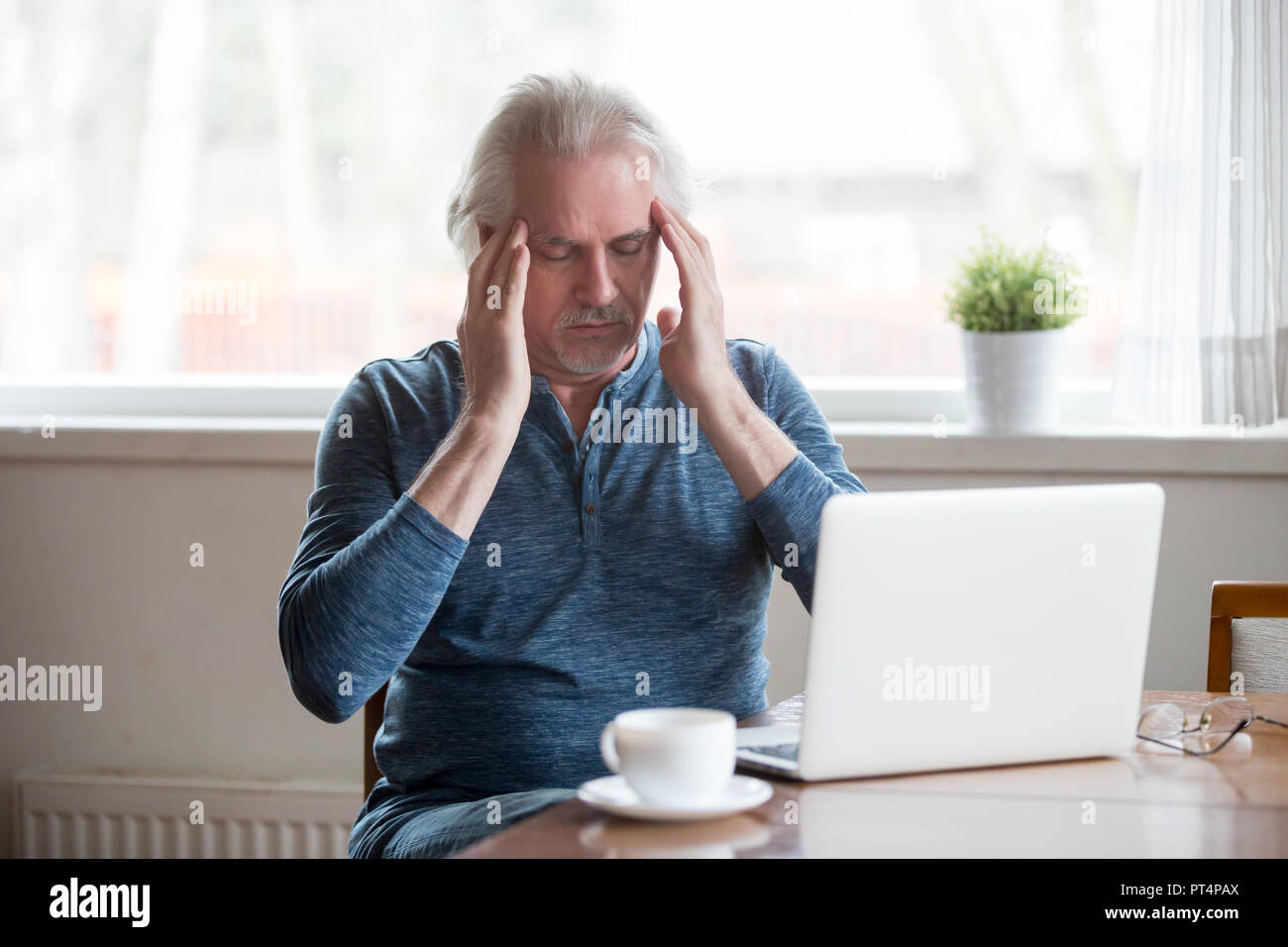 Tired senior man touching temples feeling headache working on la - Stock Image