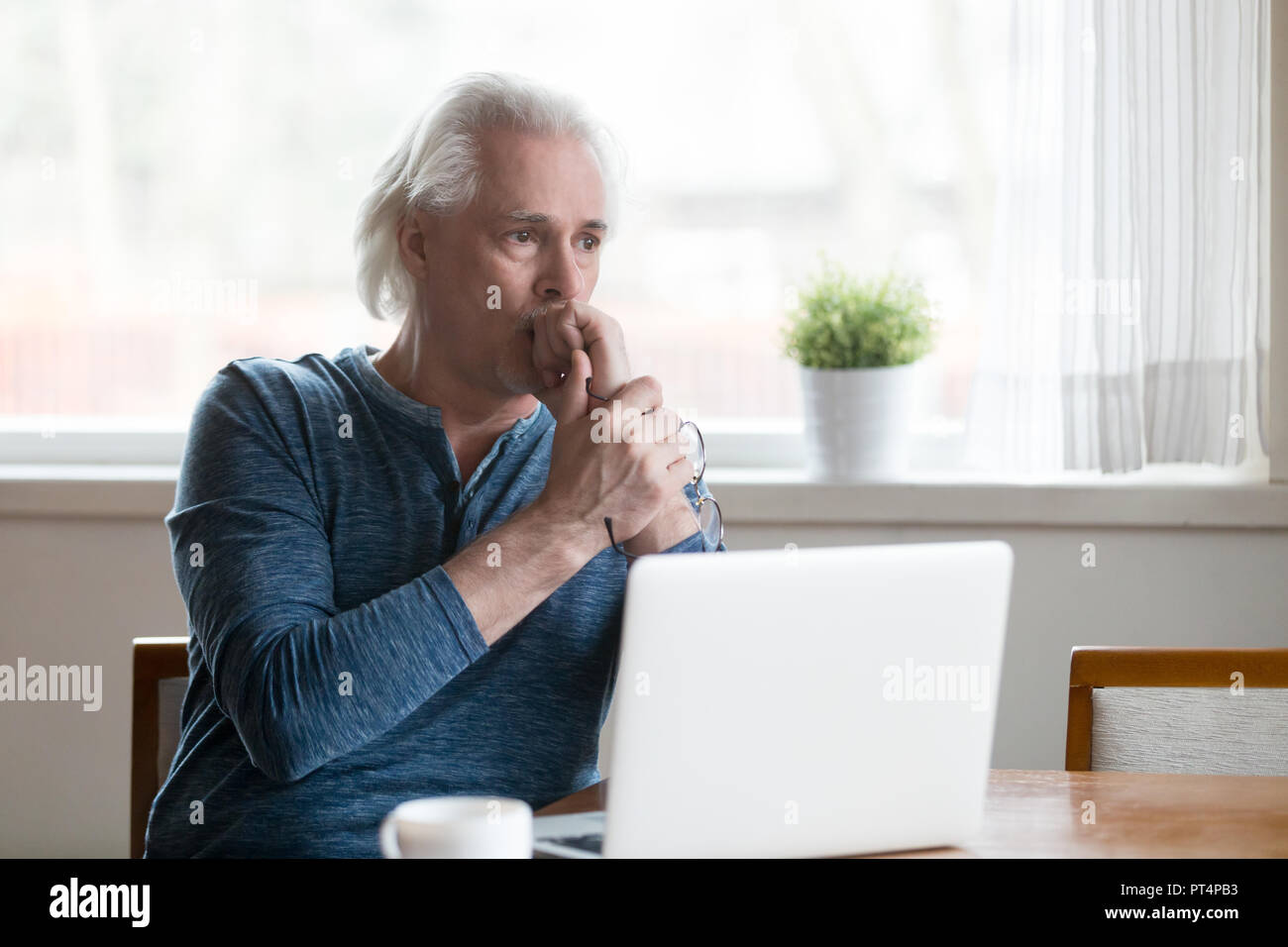 Serious thoughtful senior man looking away thinking of problem s - Stock Image