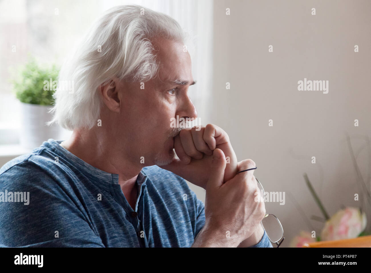 Worried serious senior man looking away feeling anxious about pr - Stock Image