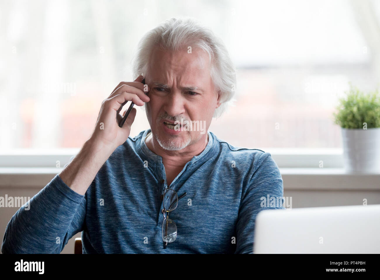 Angry senior man arguing talking on phone complaining on problem - Stock Image
