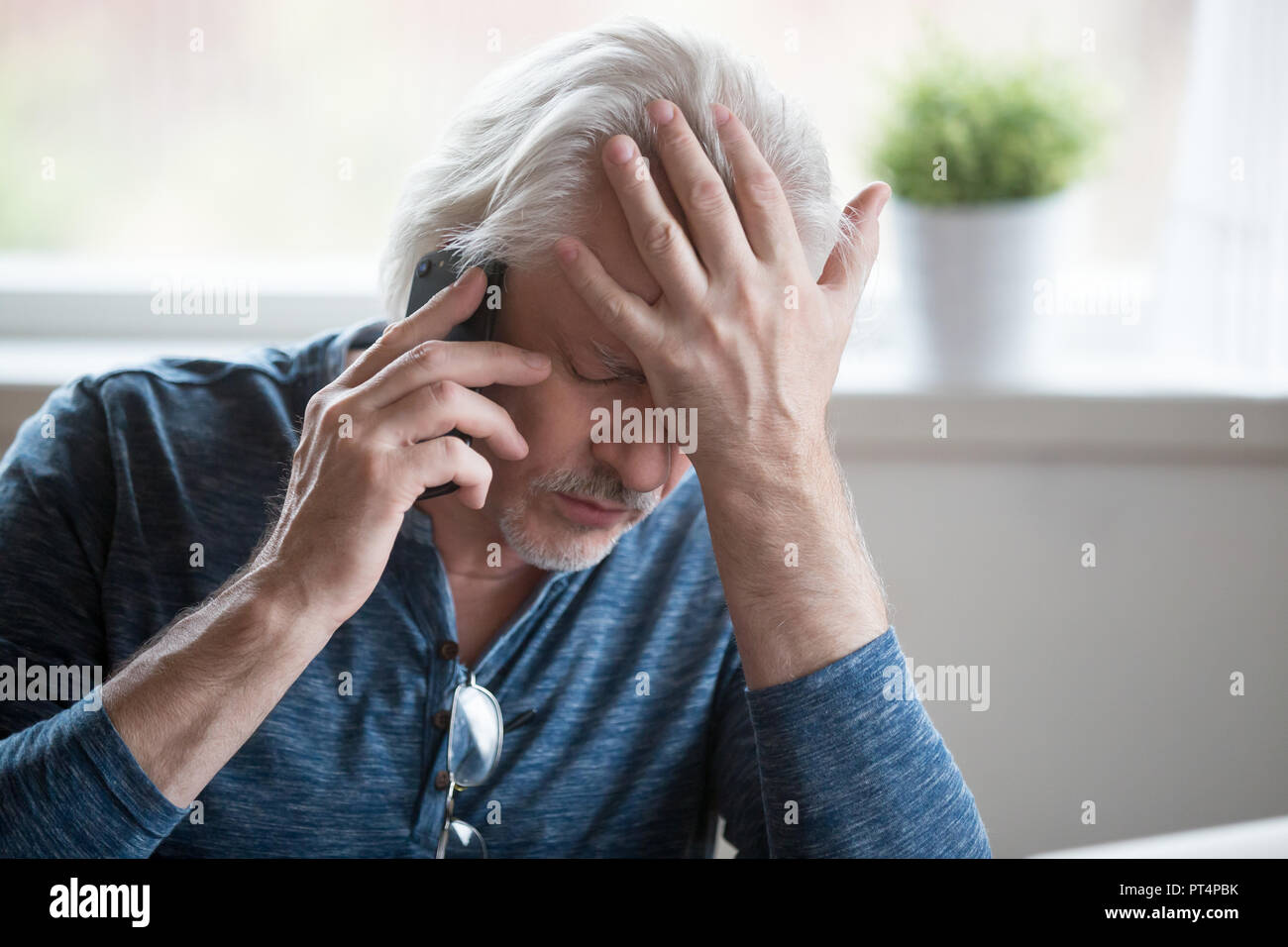 Frustrated mature man feeling upset desperate talking on the pho - Stock Image