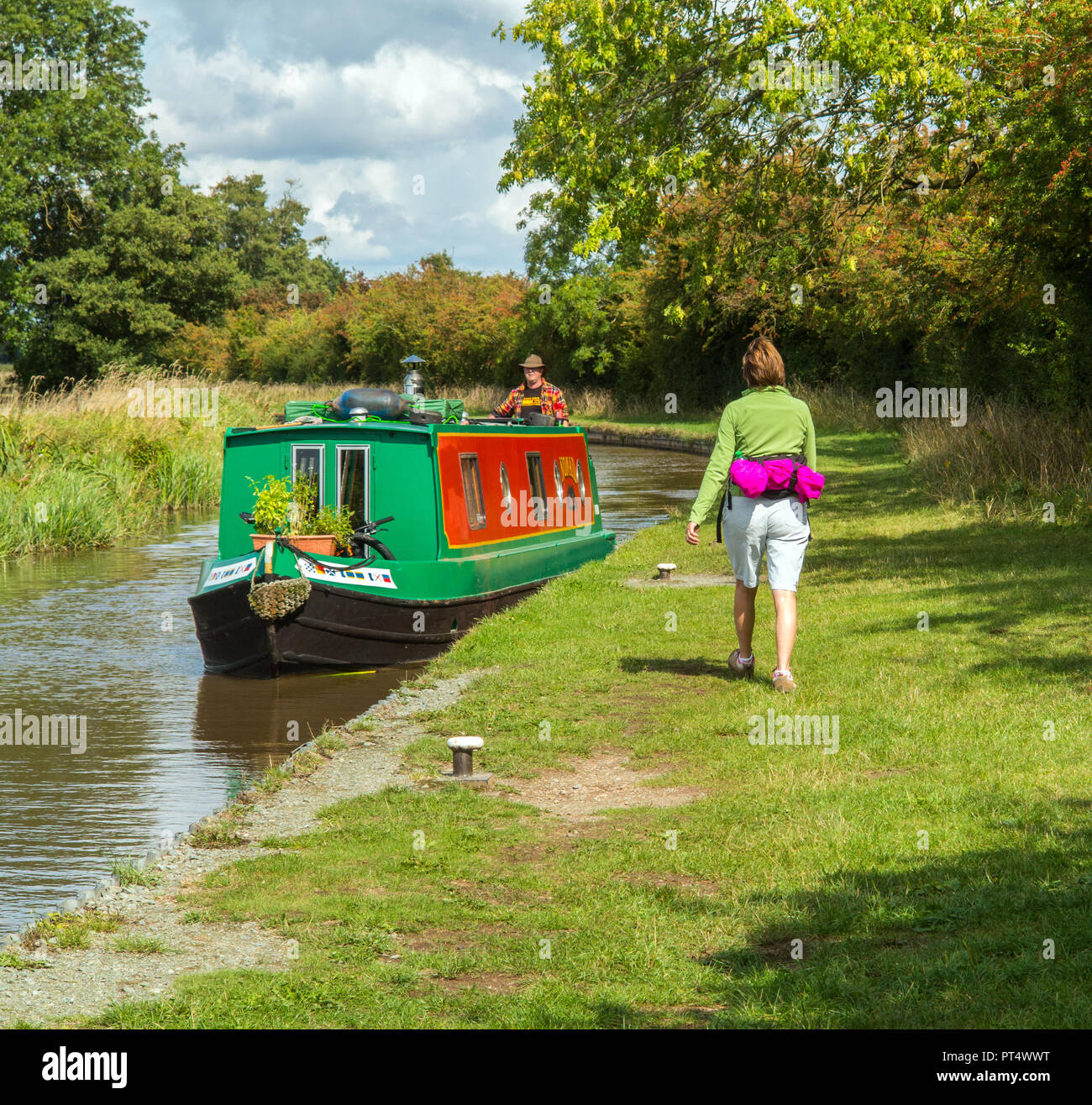 Woman walking along the towpath of the Shropshire union canal with a narrowboat passing near Wrenbury Cheshire England UK - Stock Image