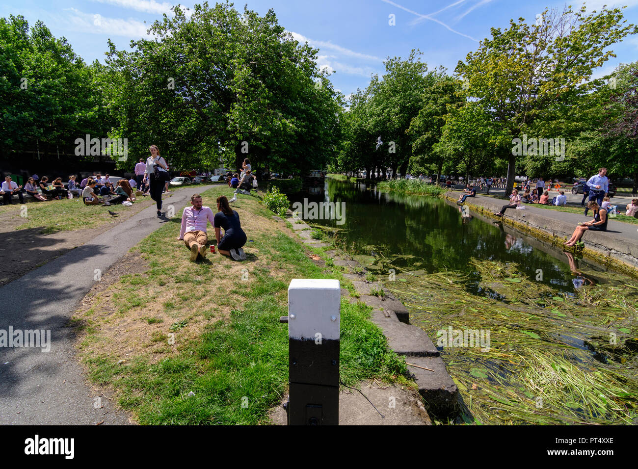 People enjoying the warm summer of 2018 during lunch time on Wilton Terrace near the Grand Canal in Dublin, Ireland - Stock Image
