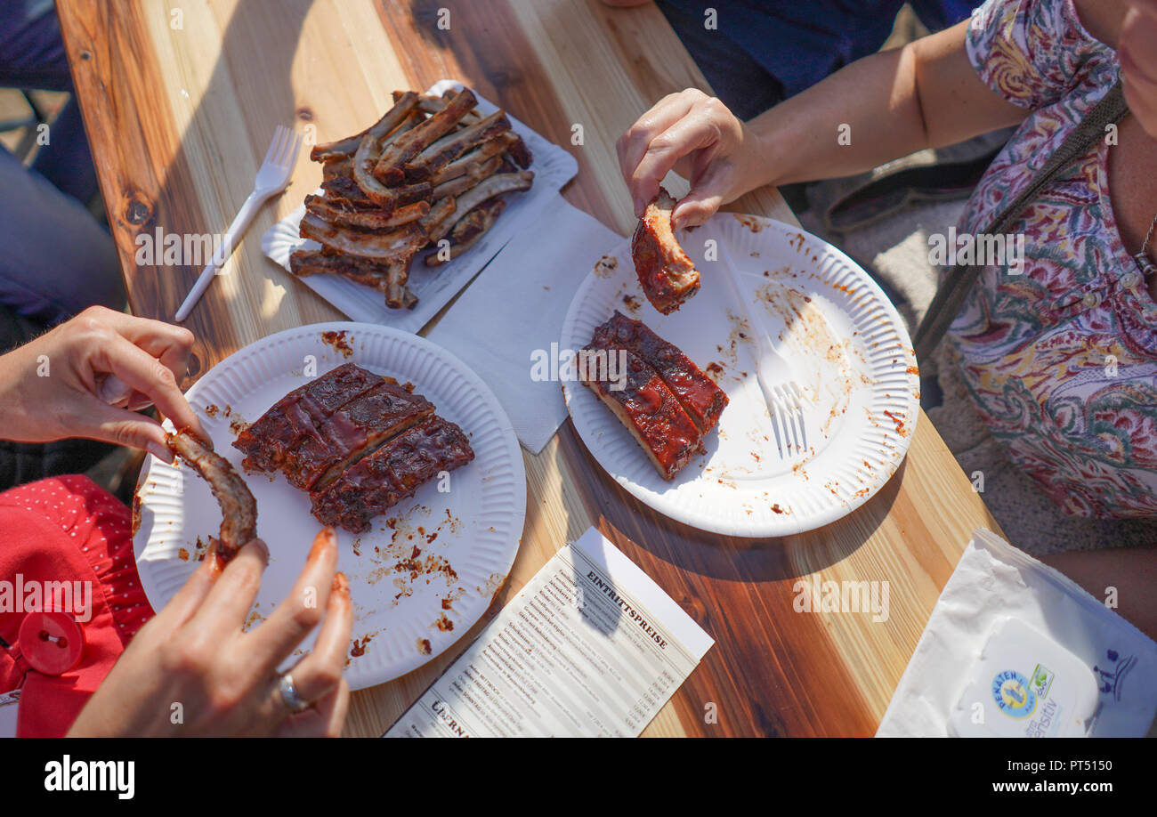 Templin, Brandenburg. 06th Oct, 2018. 06 October 2018, Germany, Templin: Two visitors enjoy spare ribs at the first 'Brandenburgische Grillmeisterschaft' in the 'El Dorado Templin'. A total of eight teams grill for the grill crown. Credit: Jörg Carstensen/dpa/Alamy Live News - Stock Image