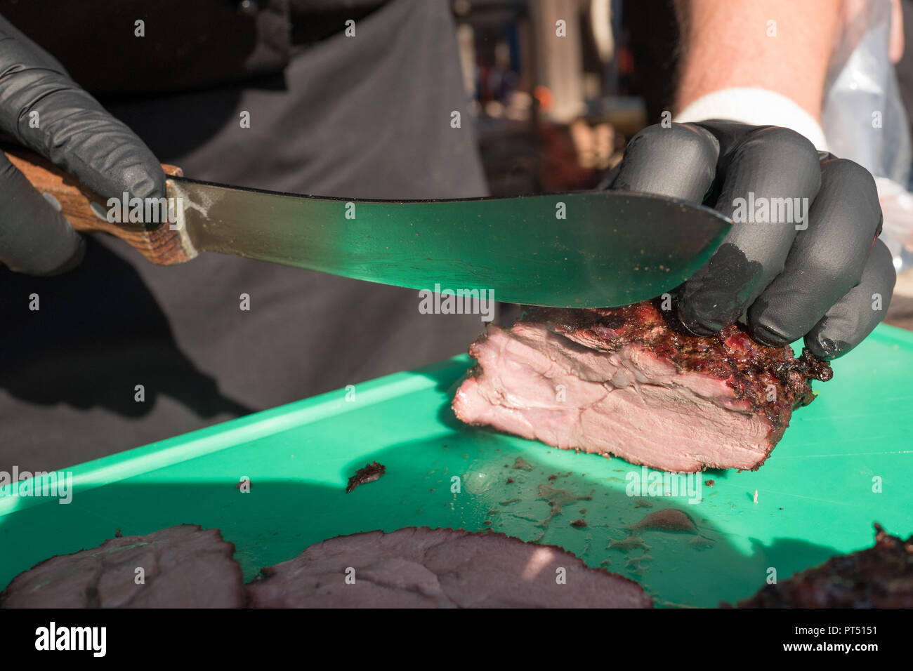 Templin, Brandenburg. 06th Oct, 2018. 06 October 2018, Germany, Templin: A grilled piece of Templin wild boar is cut into slices at the first 'Brandenburg Barbecue Championship' in the 'El Dorado Templin'. A total of eight teams grill for the grill crown. Credit: Jörg Carstensen/dpa/Alamy Live News - Stock Image