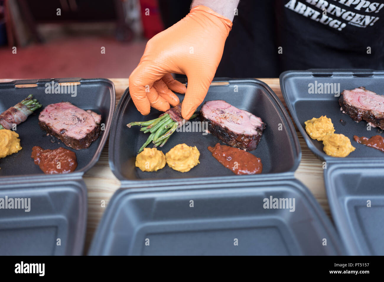 Templin, Brandenburg. 06th Oct, 2018. 06 October 2018, Germany, Templin: The team 'Born for BBQ' prepares a dish with Templiner wild boar at the first 'Brandenburgische Grillmeisterschaft' in the 'El Dorado Templin'. A total of eight teams grill for the grill crown. Credit: Jörg Carstensen/dpa/Alamy Live News - Stock Image