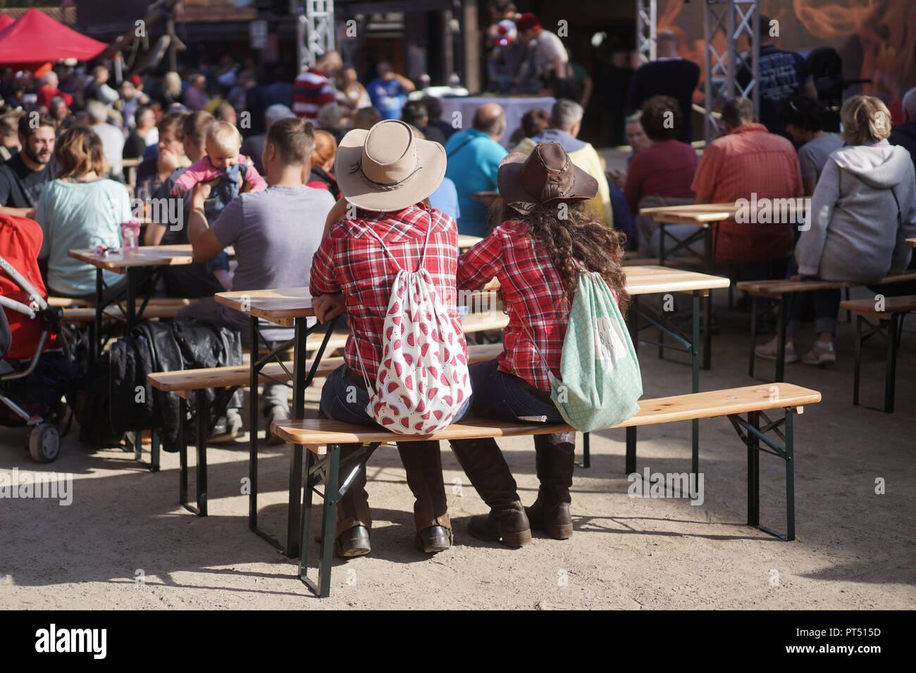 Templin, Brandenburg. 06th Oct, 2018. 06 October 2018, Germany, Templin: Two visitors are dressed in a cowboy look at the first 'Brandenburg Barbecue Championship' in the 'El Dorado Templin'. A total of eight teams grill around the grill crown. Credit: Jörg Carstensen/dpa/Alamy Live News - Stock Image