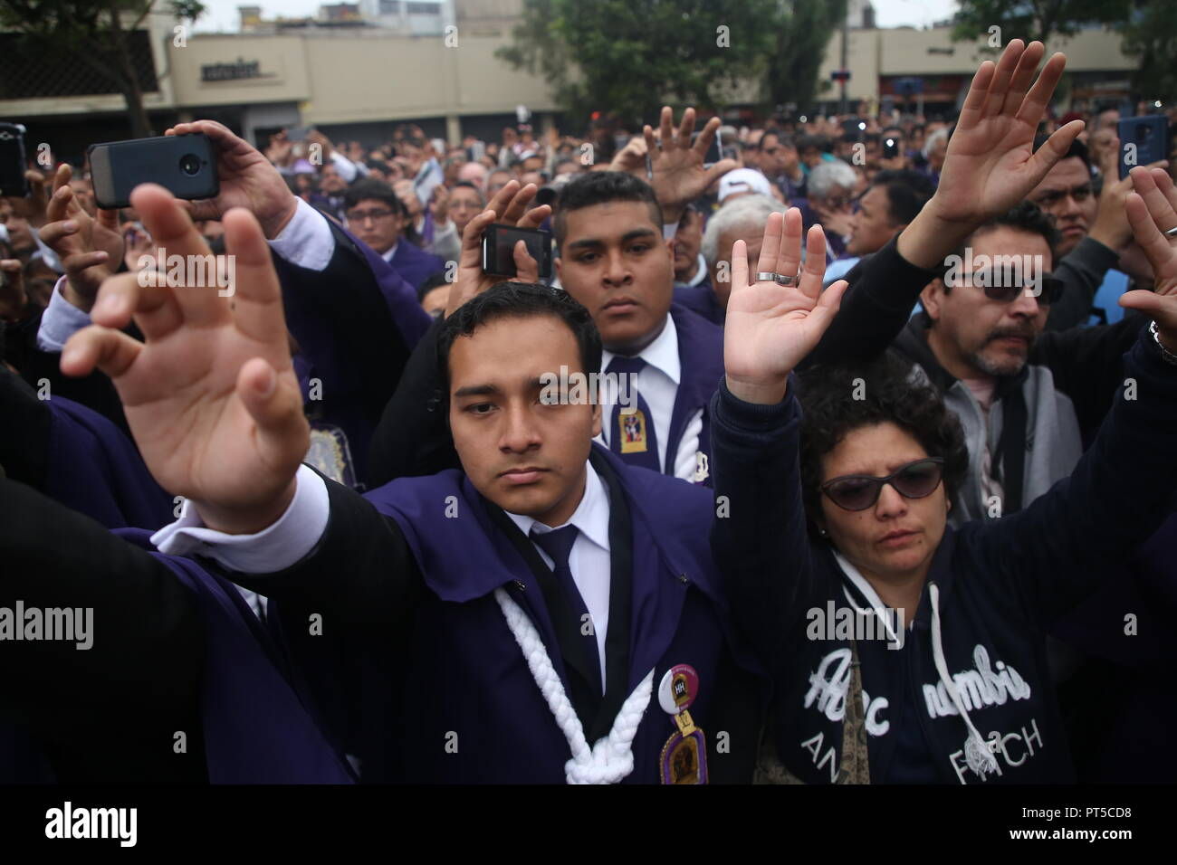 Lima, Peru. 06th Oct, 2018. Believers raise their arms during a procession in honour of the 'Senor de los Milagros' (Lord of Miracles). 'Senor de los Milagros' is a Catholic festival that is celebrated every year in Lima. Credit: Geraldo Caso/dpa/Alamy Live News - Stock Image