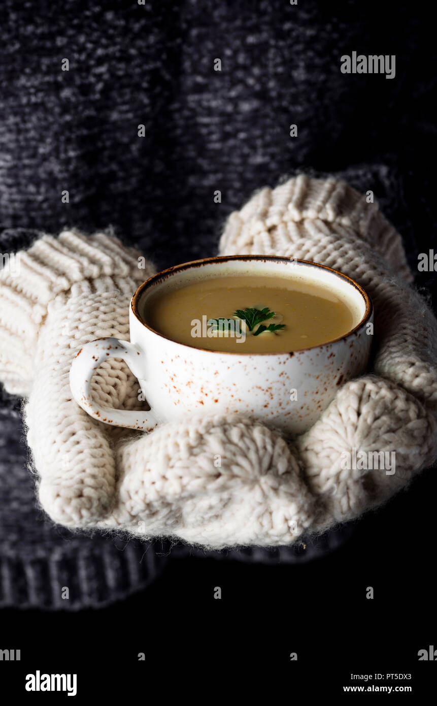 Girl in mittens holding a cup of soup - Stock Image