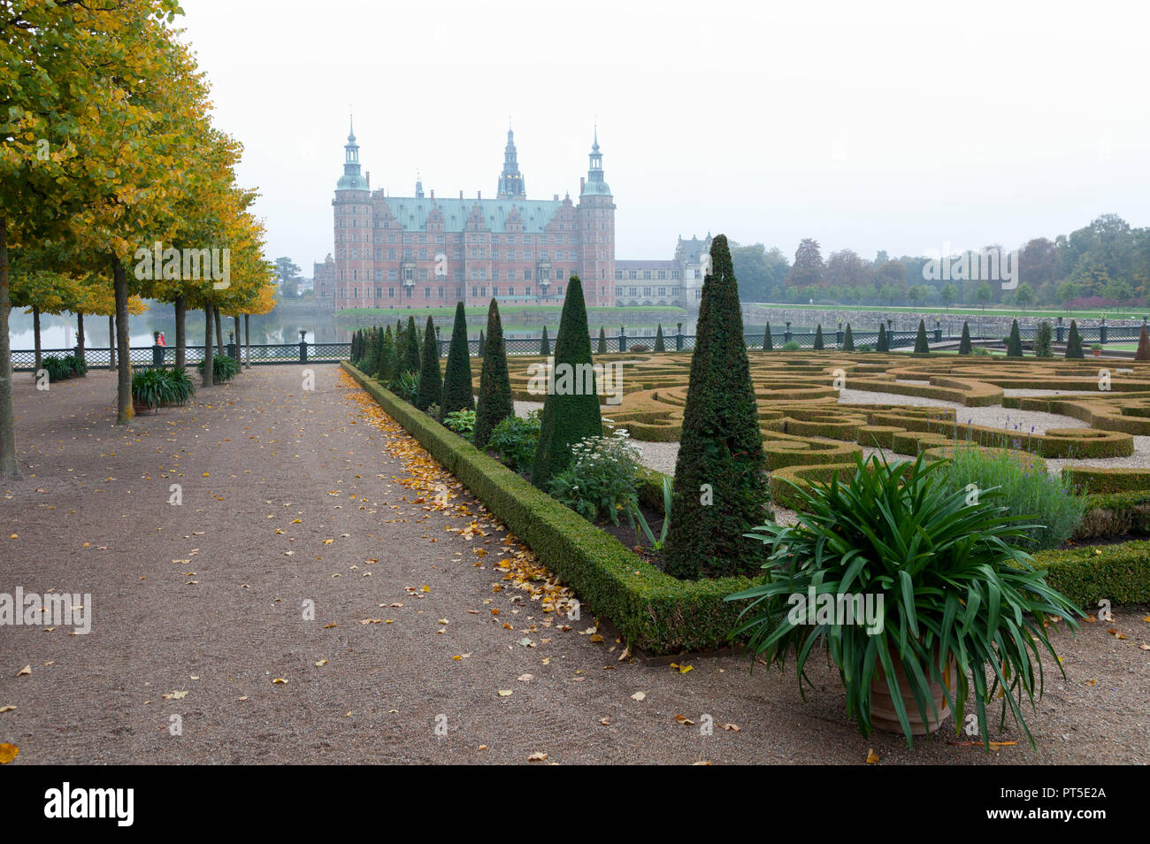 Frederiksborg Castle and the Baroque Garden in Hillerød, North Sealand, Denmark, on a foggy autumn day - Stock Image