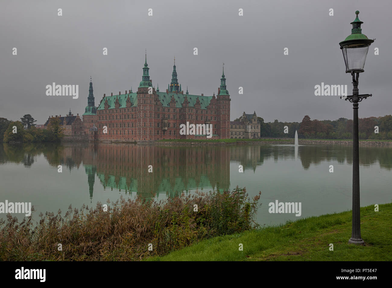 Frederiksborg Castle in Hillerød, North Sealand, Denmark, on a foggy autumn day - Stock Image