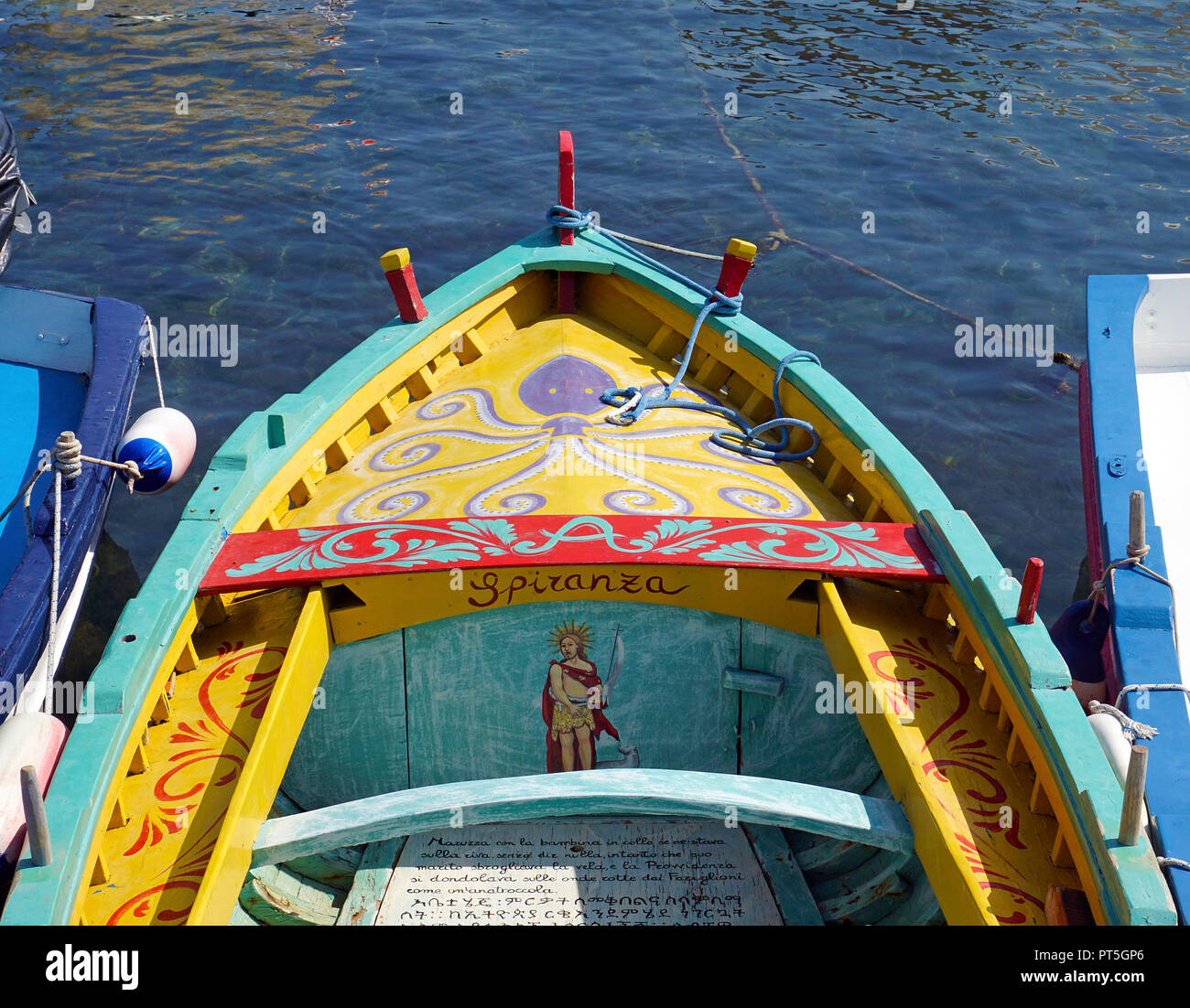 Colourful painted fishing boat with religious text at harbour of fishing village Aci Trezza, comune of Aci Castello, Catania, Sicily, Italy Stock Photo