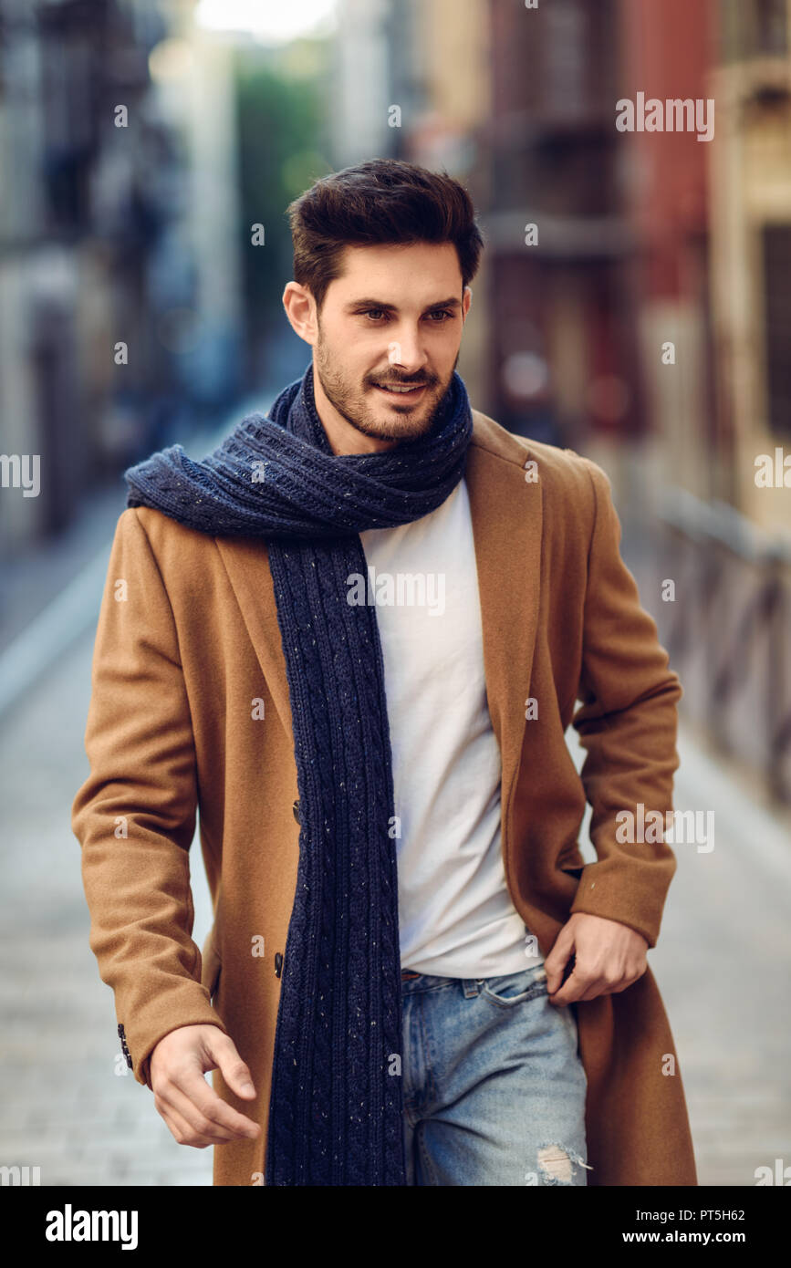 Young man wearing winter clothes in the street. Young bearded guy with  modern hairstyle with coat, scarf, blue jeans and t,shirt.