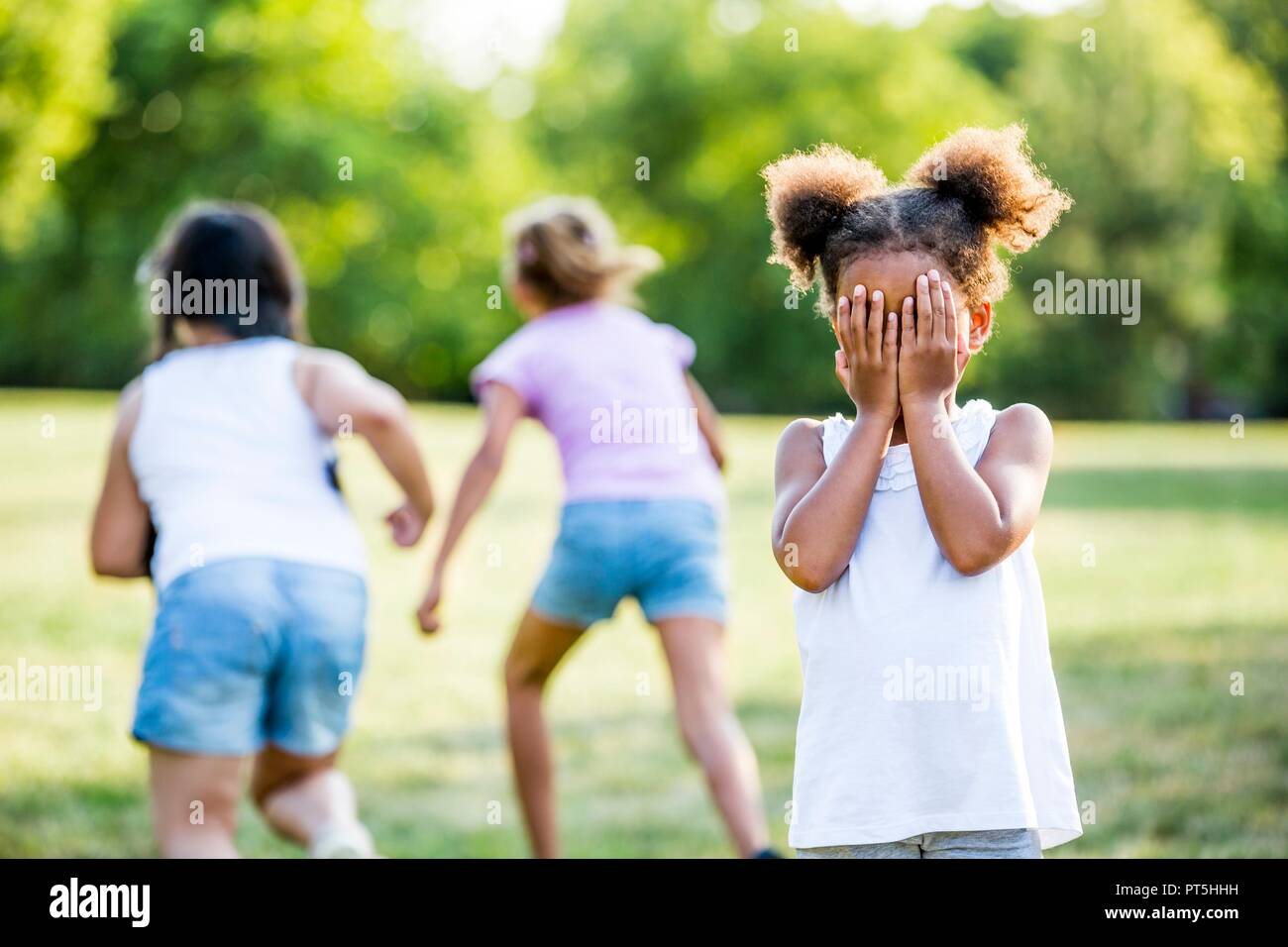 Girls playing hide and seek game in park. - Stock Image