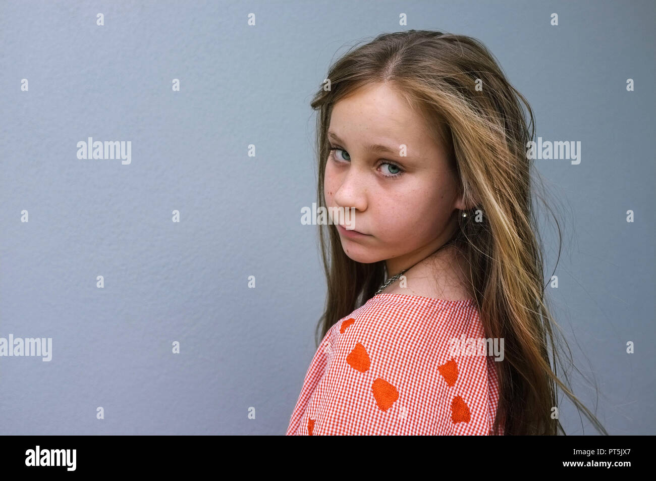 Portrait of a pre-teen girl looking over her shoulder, against a grey wall. Stock Photo