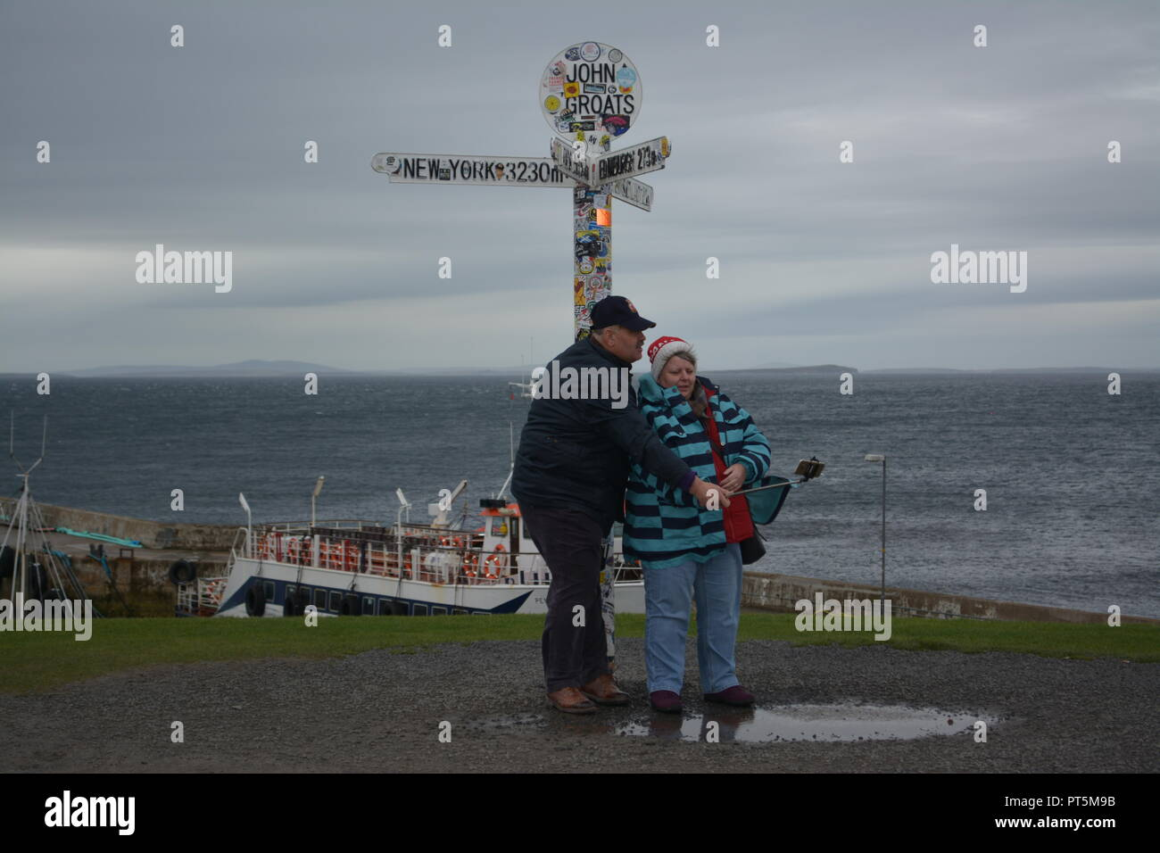 Elderly Tourists holidaymakers taking a selfie photograph under the John O'Groats signpost Caithness Scotland Great Britain UK United Kingdom - Stock Image