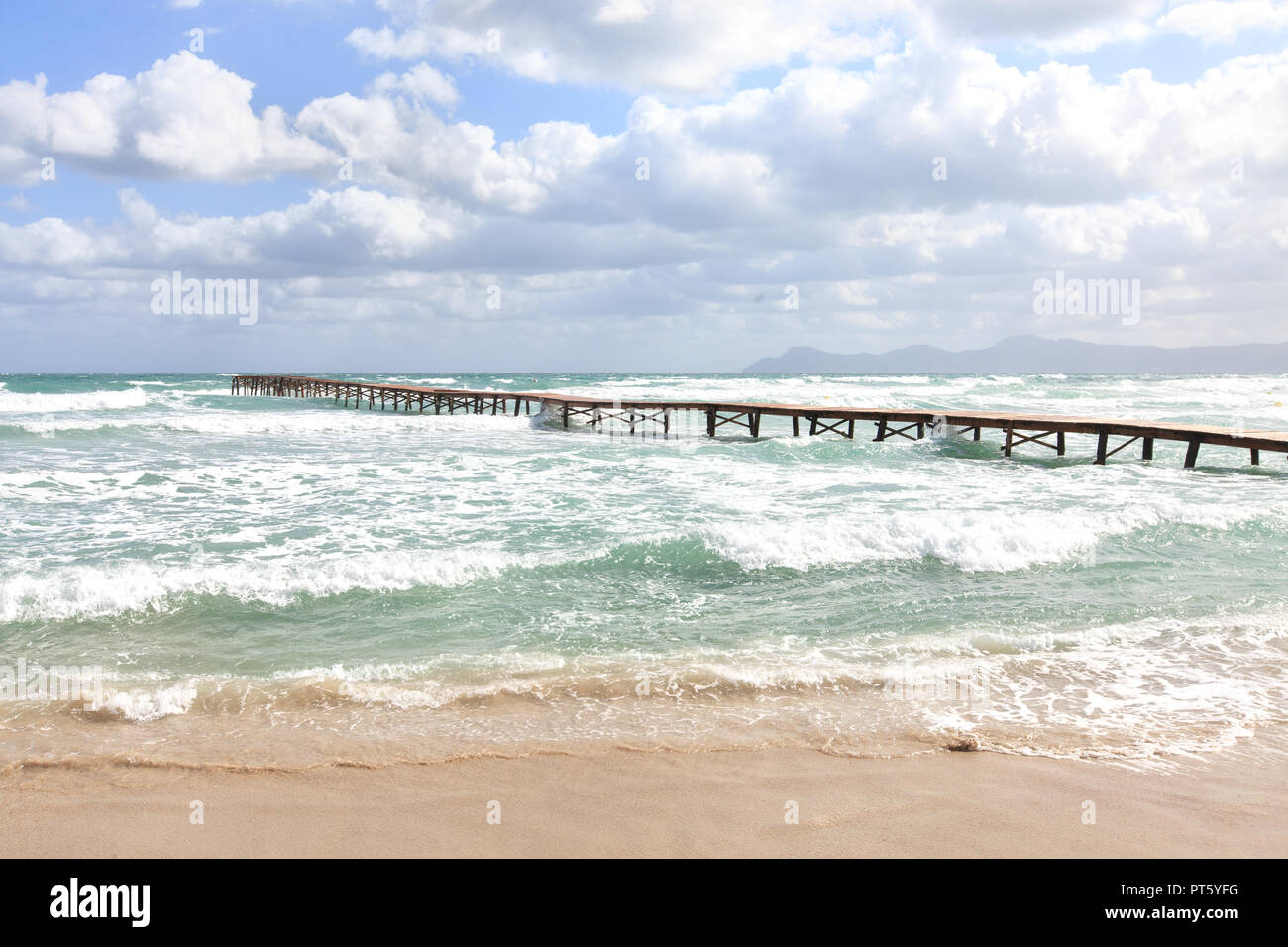 Europe Spain North Mallorca Playa de Muro, long wooden jetty in the bay of Alcudia during violent storm - Stock Image
