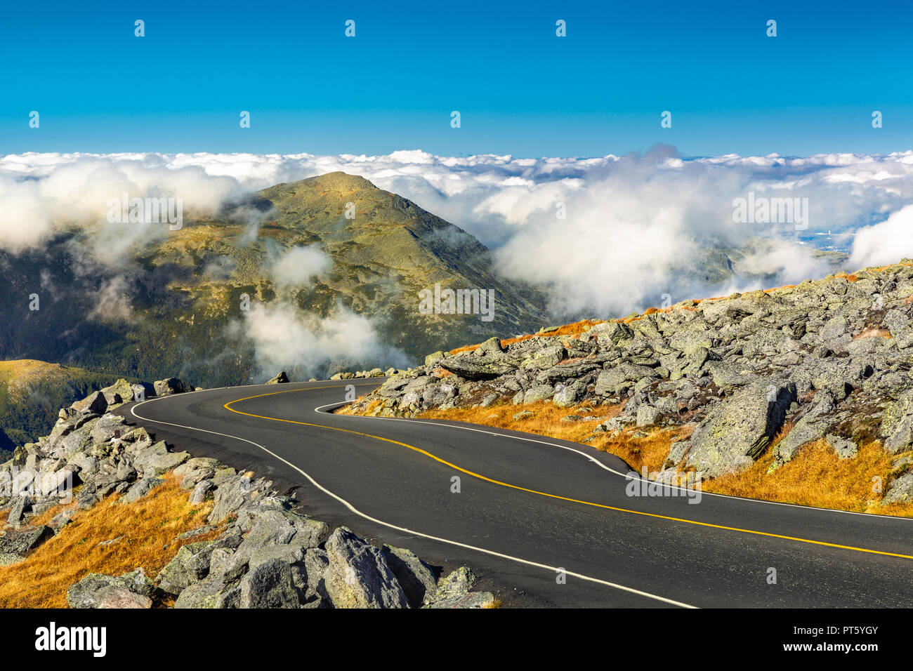 Winding road descending from Mount Washington, NH on a sunny autumn afternoon. Mount Jefferson peak stands above a thick layer of fluffy clouds. - Stock Image
