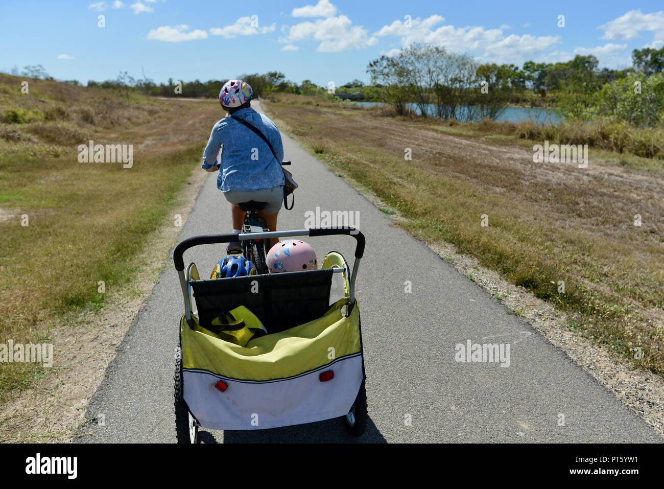 Woman riding a bicycle with a bicycle trailer for children, Townsville, QLD, Australia Stock Photo