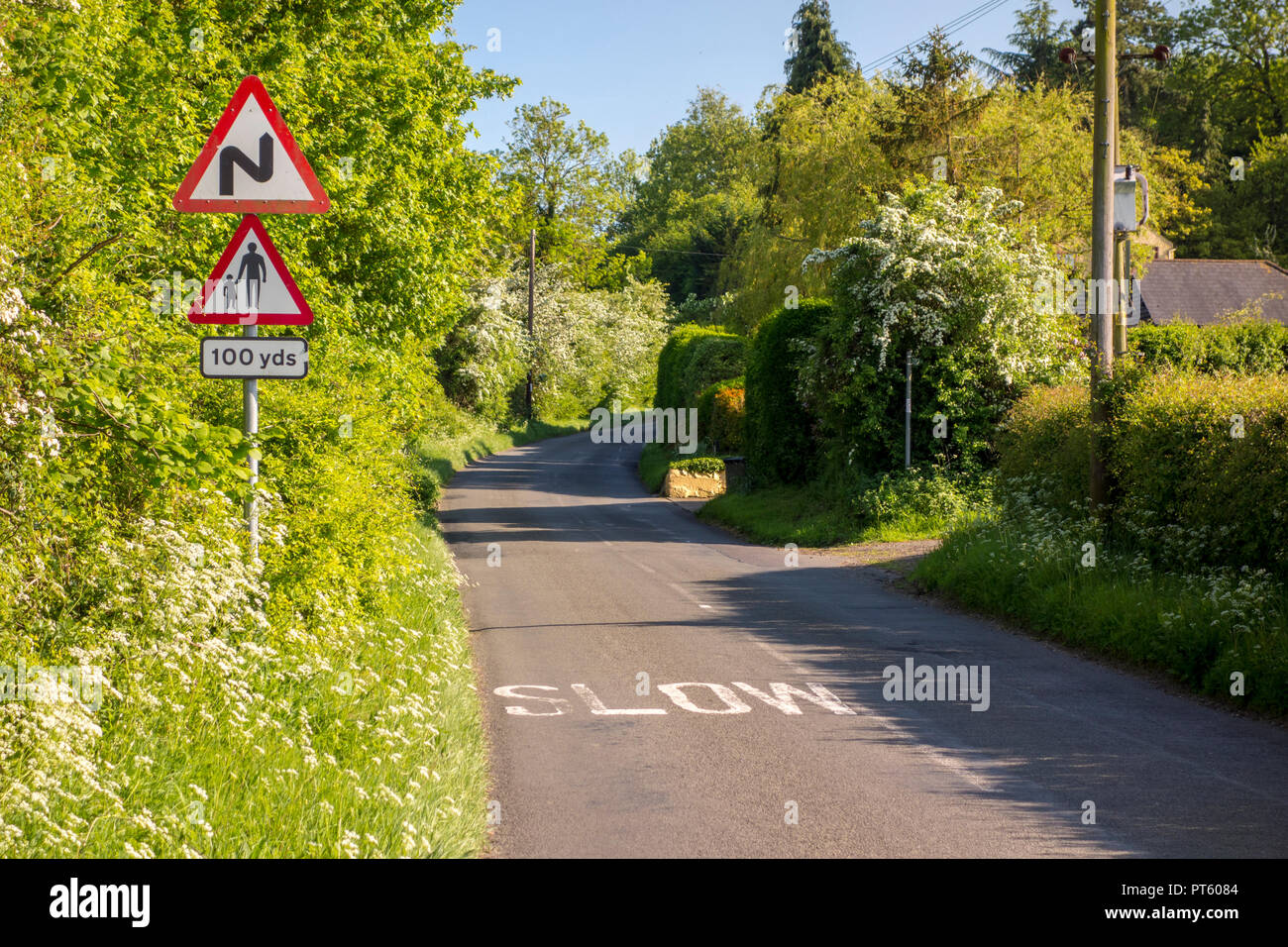 Warning triangle road signs for bends and pedestrians with slow sign on a British country lane, Sharpenhoe, UK - Stock Image