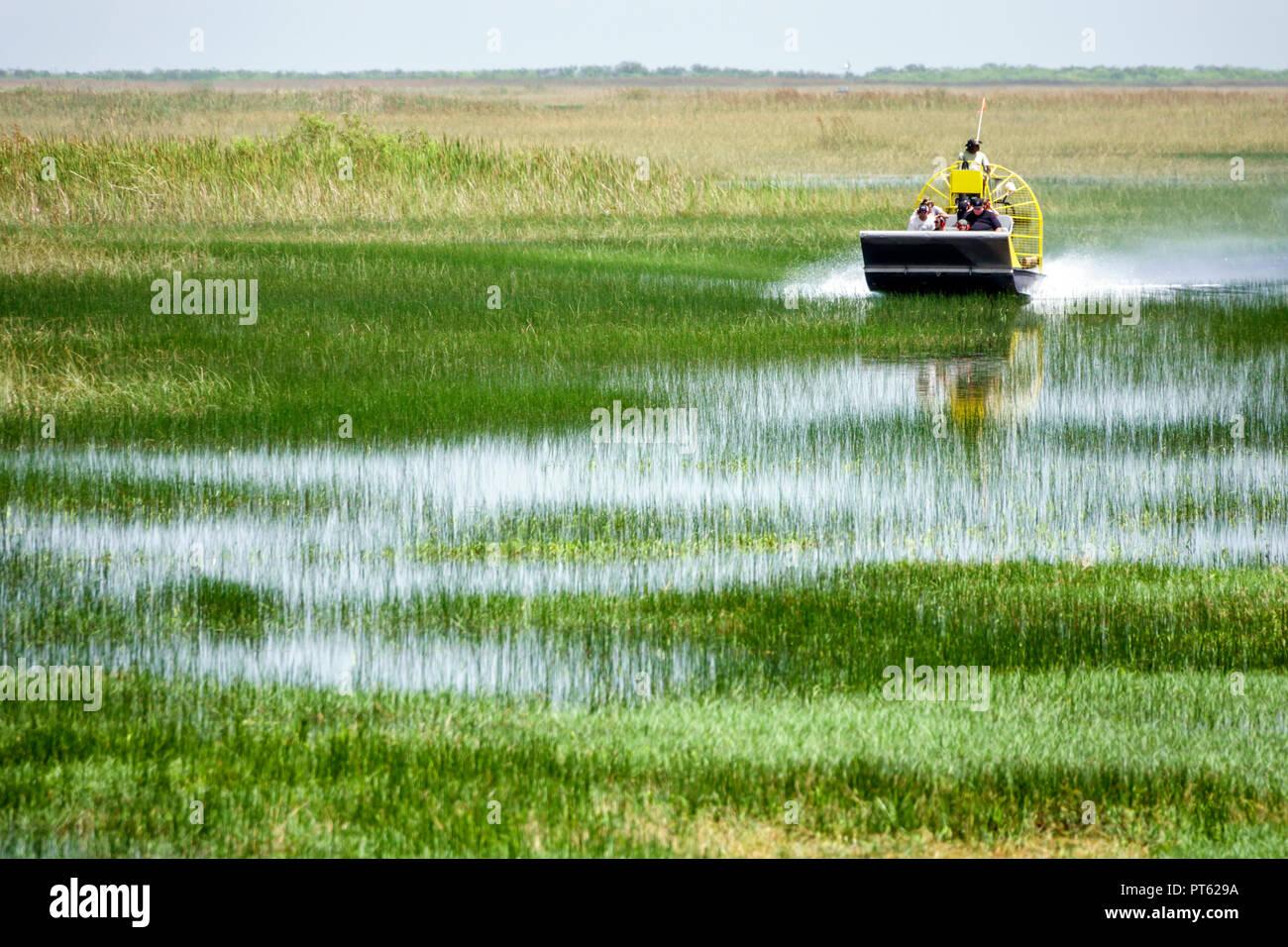 Miami Florida Everglades National Park airboat rider riders Black family couple man woman grass sawgrass water flat flatness pilot - Stock Image