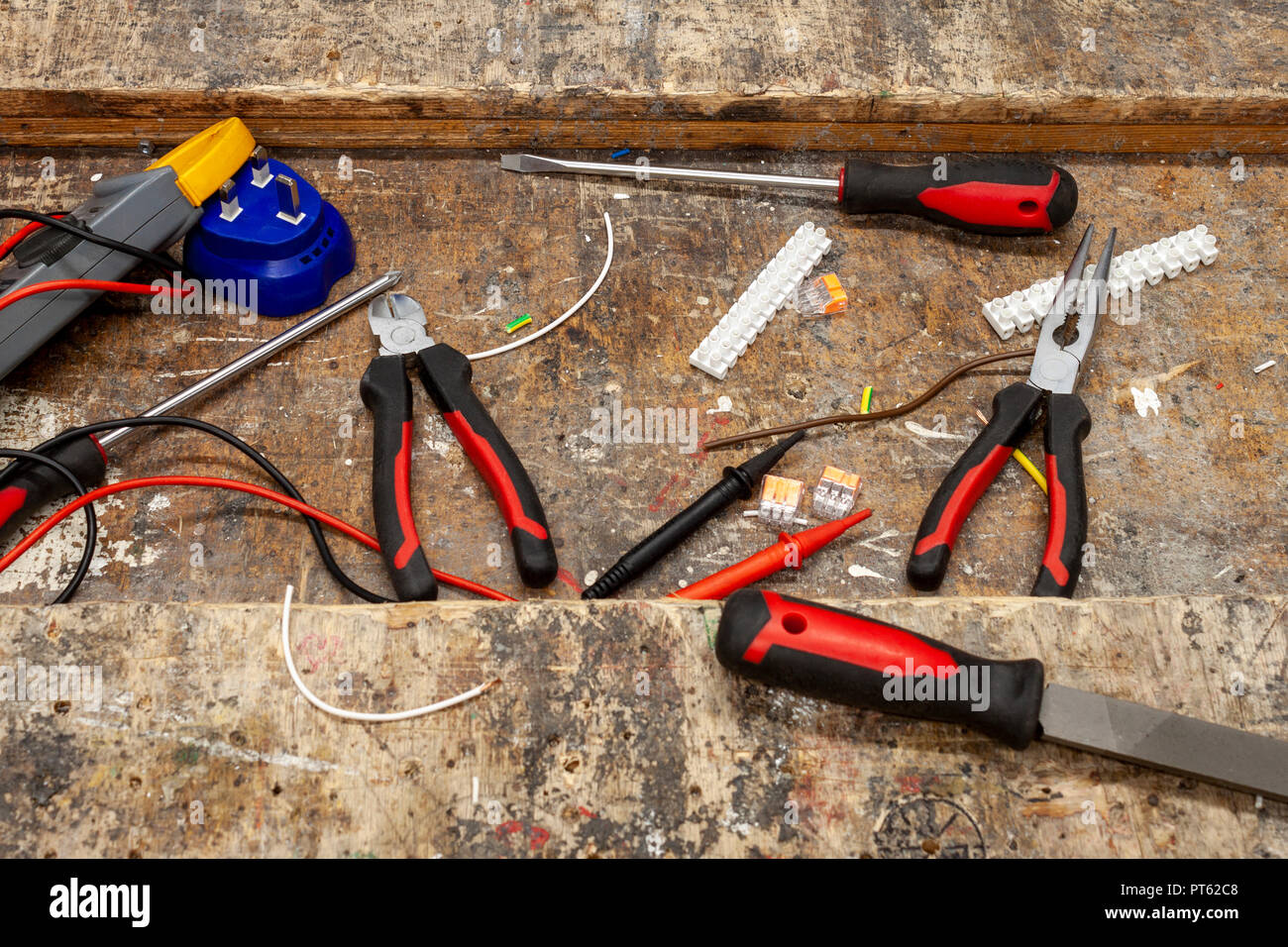 Long nose pliers and various electrical hand tools on an old wooden workbench with scraps of copper wire and connectors - Stock Image