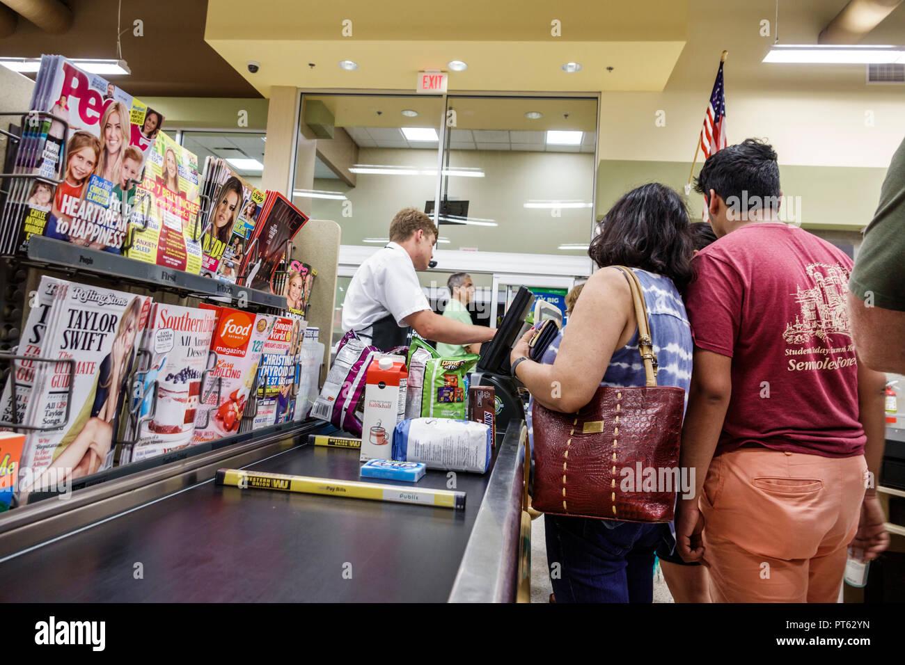 St. Saint Petersburg Florida Publix Grocery Store supermarket inside display sale magazines checkout cashier line queue conveyor belt man woman couple - Stock Image