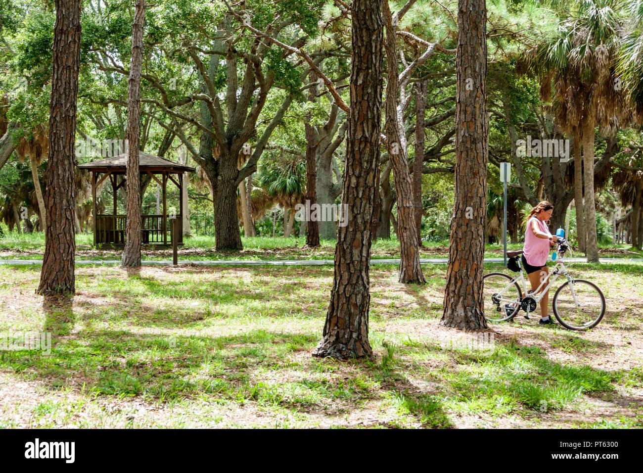 St. Saint Petersburg Florida Bay Pines War Veterans Memorial Park woman bicycle trees - Stock Image