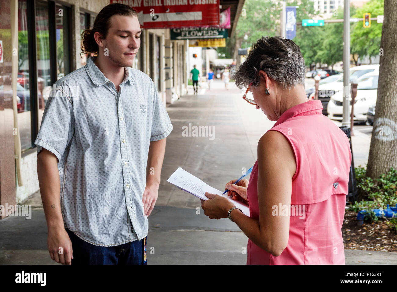 St. Saint Petersburg Florida Central Avenue survey questionnaire opinion poll woman man asking questions street sidewalk Stock Photo