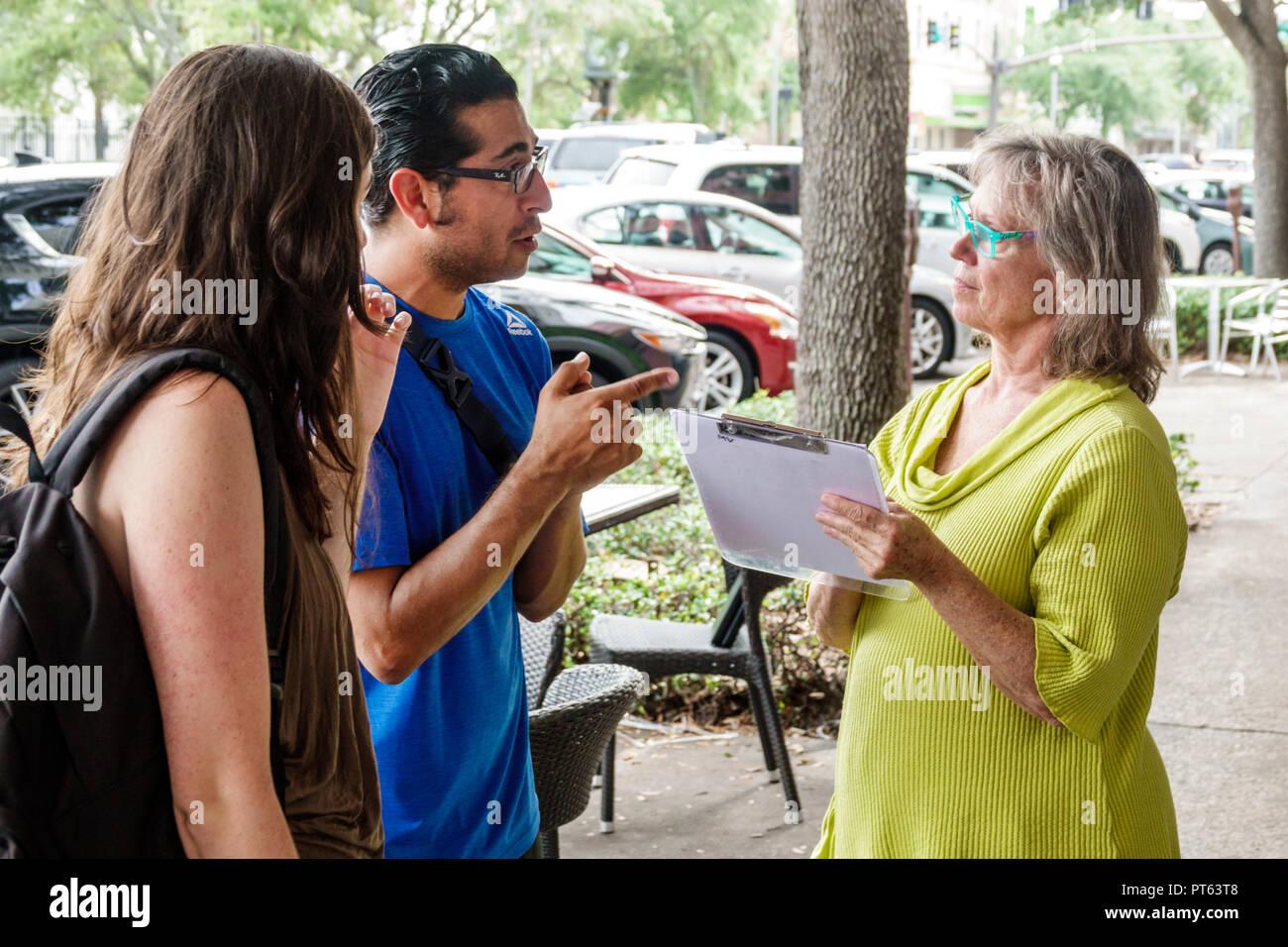 St. Saint Petersburg Florida Central Avenue survey questionnaire opinion poll woman man asking questions street sidewalk couple - Stock Image