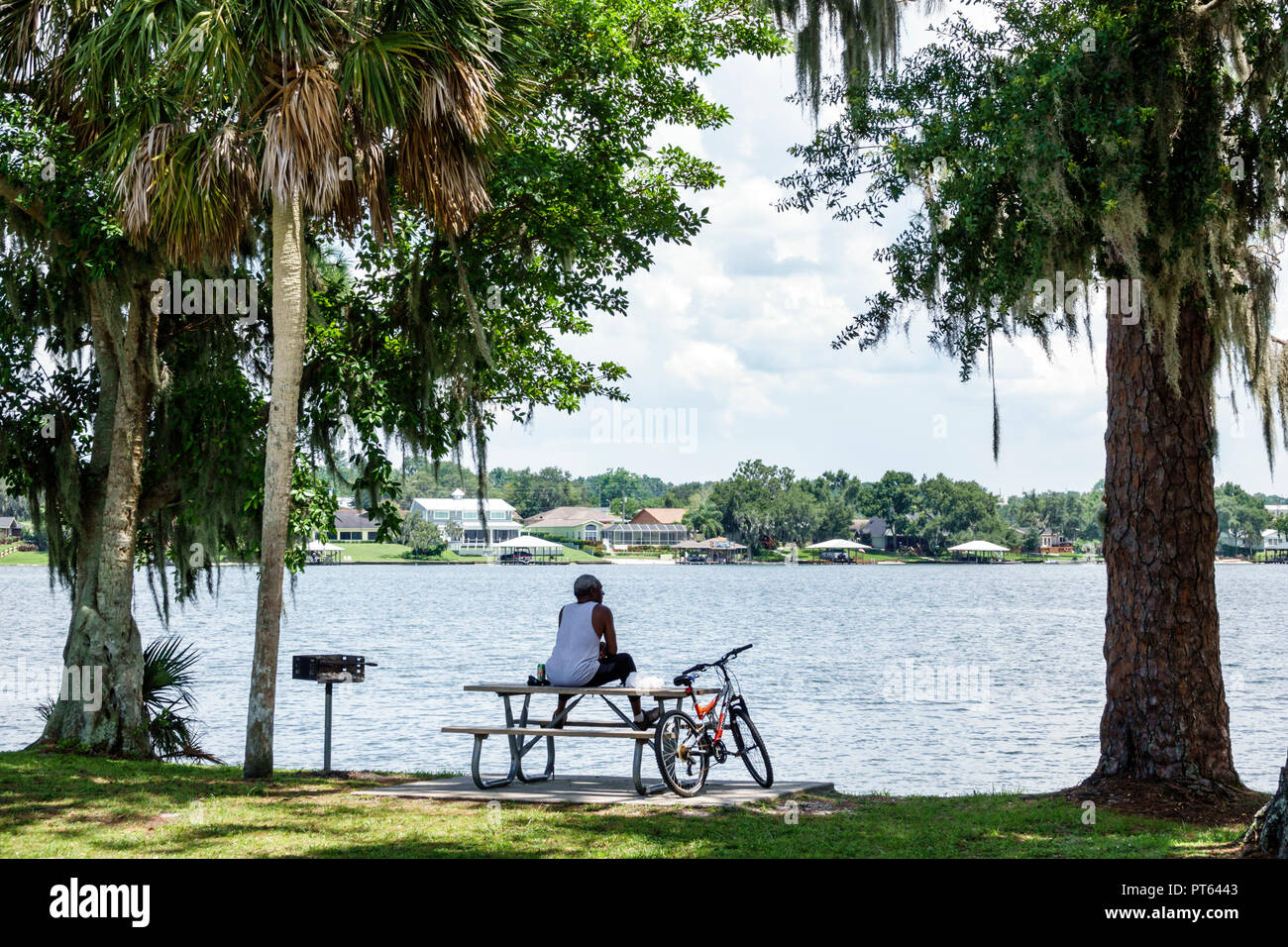 Lake Placid Florida Lake June-in-Winter H. L. Bishop Park man bicycle picnic table - Stock Image