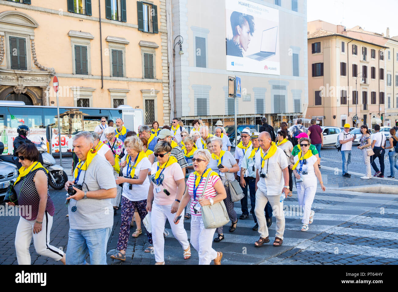 Organised tour group in Rome with tourists wearing yellow scarves,Rome,Italy - Stock Image