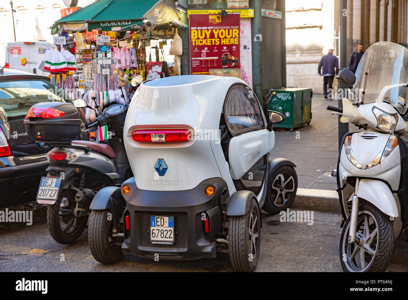 Renault Twizy electric vehicle car parked in a small space between scooters in the centre of Rome,Italy Stock Photo