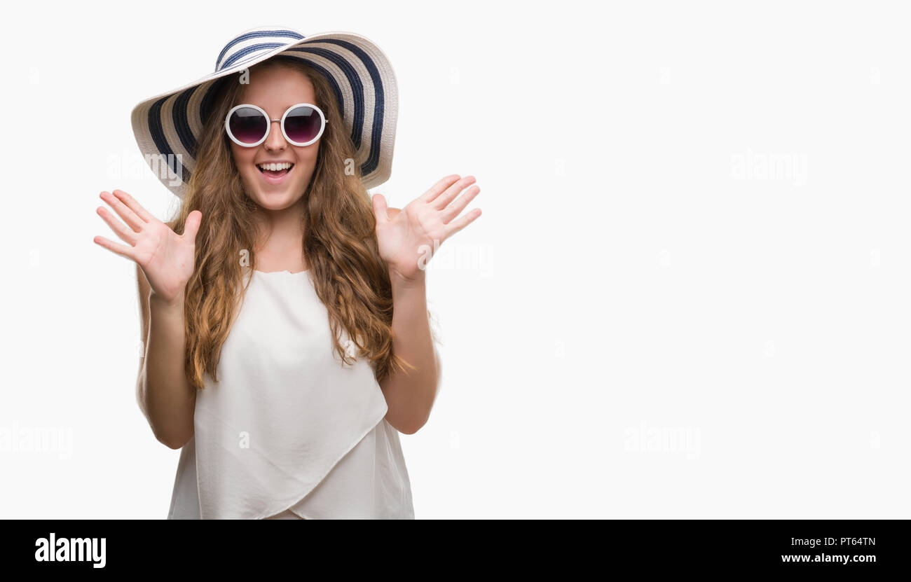 Young blonde woman wearing sunglasses and summer hat very happy and excited, winner expression celebrating victory screaming with big smile and raised - Stock Image