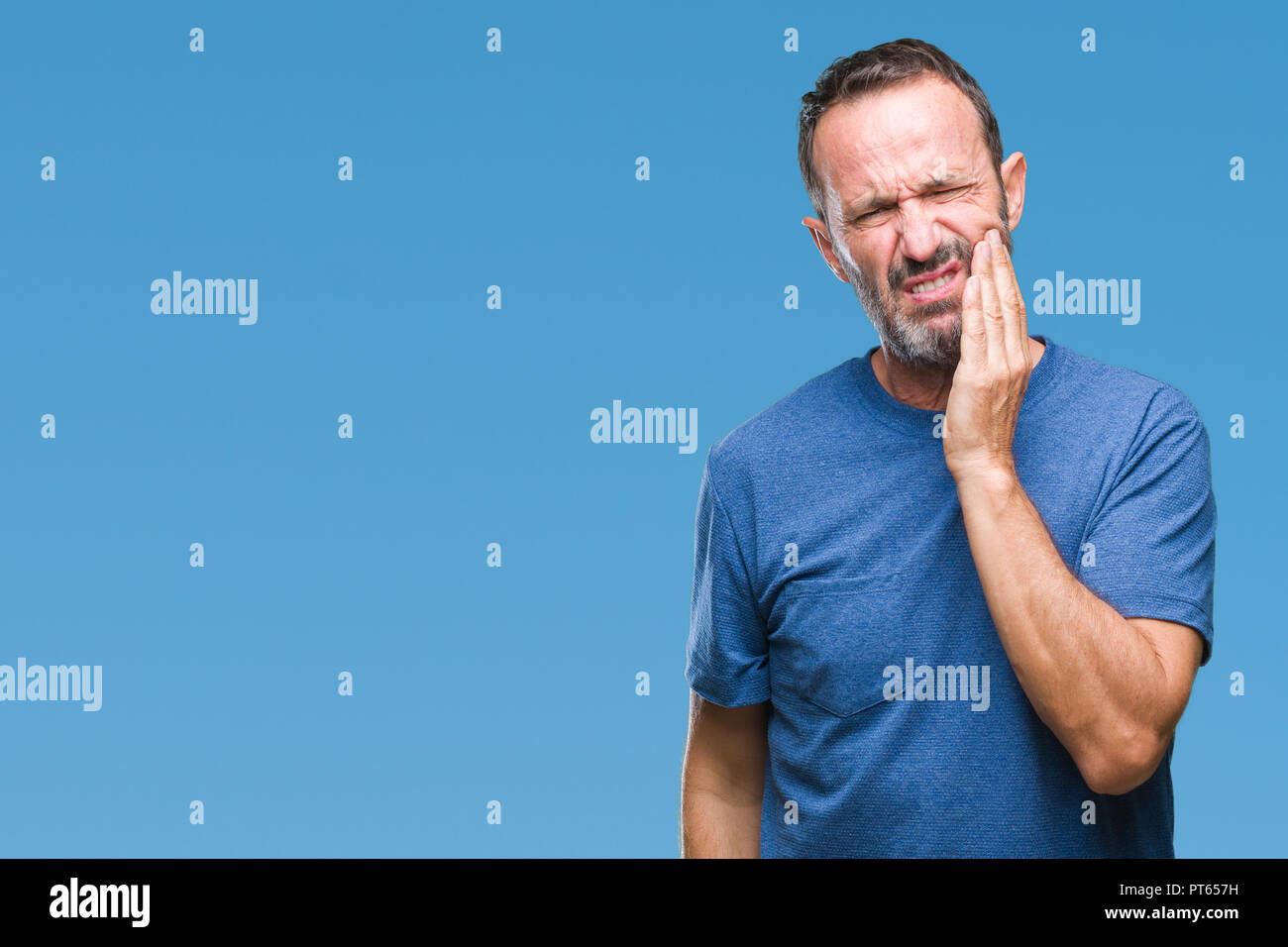 Middle age hoary senior man over isolated background touching mouth with hand with painful expression because of toothache or dental illness on teeth. Stock Photo