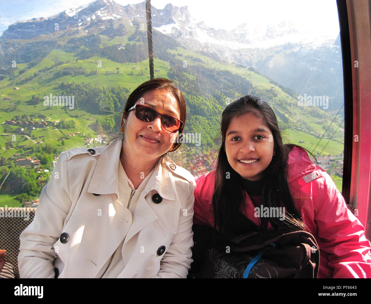 MOTHER AND DAUGHTER IN CABLE CAR TO MOUNT TITLIS, SWITZERLAND - Stock Photo