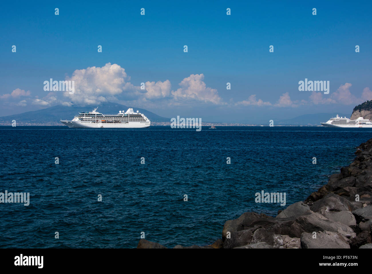 cruise ships moored off the coast of the town of sorrento Italy with mount Vesuvius in the background - Stock Image