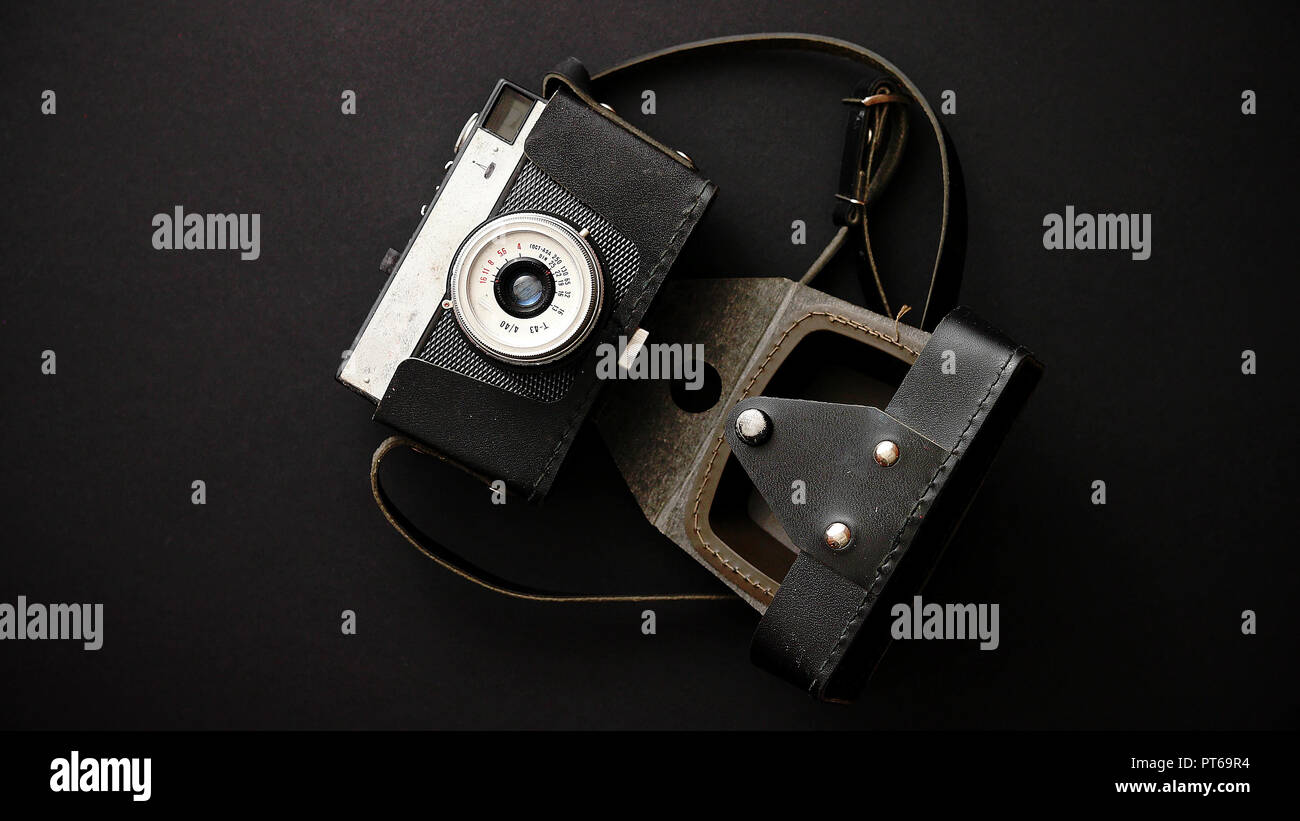 Old retro film camera in leather case on black background Stock Photo