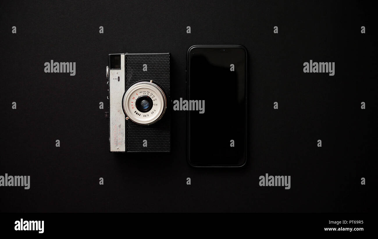 Old retro film camera and modern smartphone on black background - Stock Image