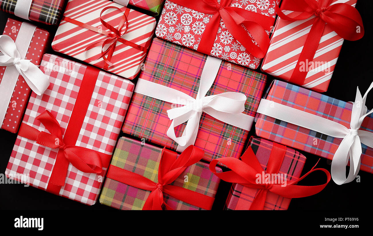 Top view of wrapped Christmas presents laid on the black background - Stock Image